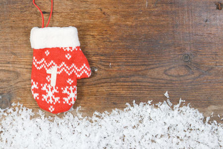 Advent calendar with red mittens and snow on wooden background