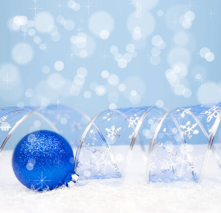 Christmas Decoration with a blue ball, curved ribbon on bokeh background with copyspace for text Stock Photo