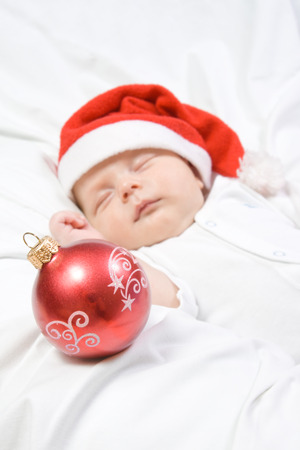 Adorable baby boy sleeping in christmas hat with a red Christmas ball on white blanket