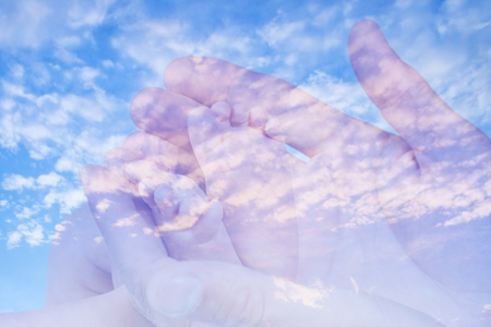 Sweet baby feet in his father hands in double exposure with cirrus clouds against the blue sky background
