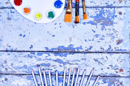 Set of watercolor aquarell rainbow paints and brushes on vintage wooden background. Top view. Stock Photo