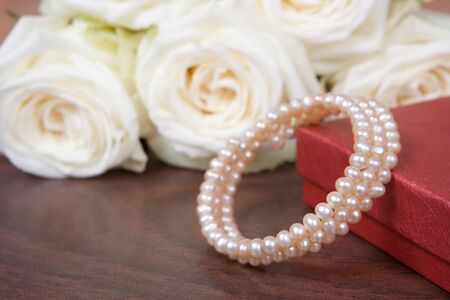 glamour pearl beads and the white roses on a wooden background