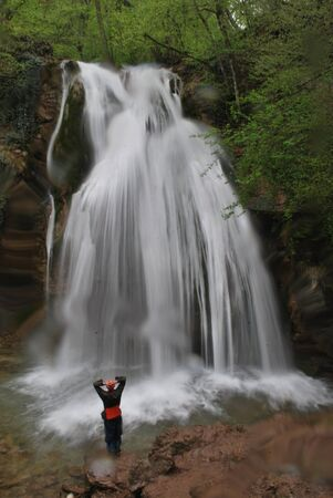 relaxes: Tourist relaxes looking at waterfall