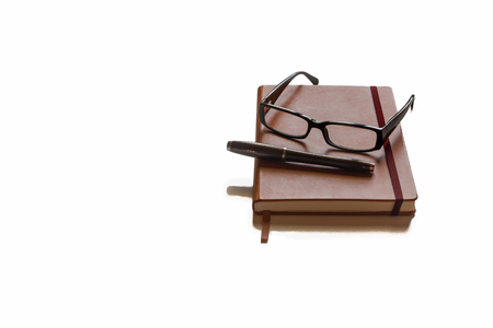 novelist: Glasses and pen on top of brown agenda with white background