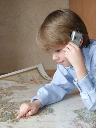 schoolkid search: Foto del ni�o con un tel�fono celular, se inclin� por encima de una tarjeta del mundo