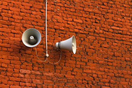 public address: Speakers hanging on an old brick wall Stock Photo