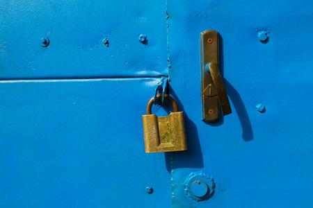 Blue metal door with a old brass padlock. photo