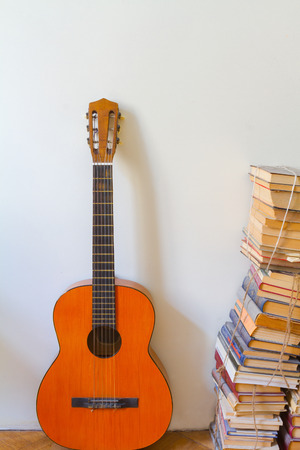 An acoustic guitar and a pile of old dusty books lying on a floor. photo
