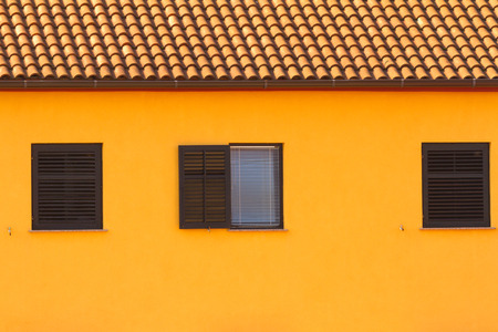 mediterranian: The yellow wall with tile roof and the window, mediterranian architecture.