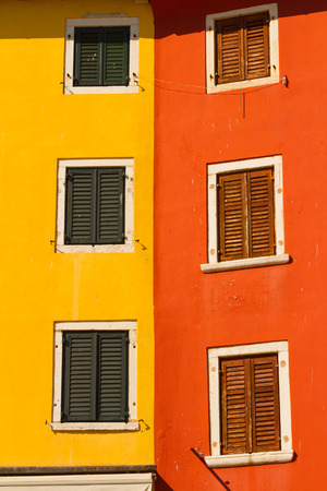 mediterranian: The colored wall and the windows with shutters, mediterranian architecture. Stock Photo