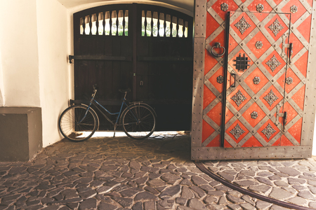 ornamentals: Bicycle near old castle gate with metal ornamentals.