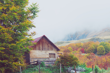 abandoned warehouse: Mountains in autumn. Abandoned warehouse in a highlands. National nature park Durmitor, Montenegro. Tinted and filtered photo. Stock Photo