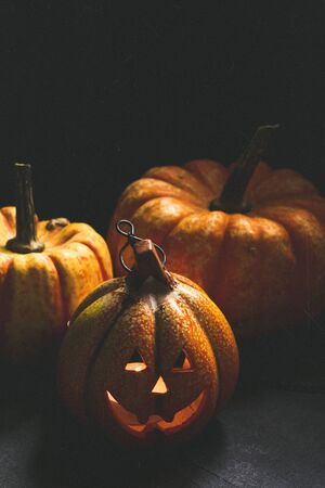 Shining Halloween lantern surrounded by natural pumpkins