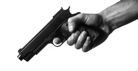 triggers: hand holding a gun in black and white