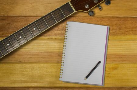 songwriter: Note and guitar on the wooden floor.