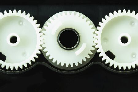 meshing: White plastic gear components of the printer. Stock Photo