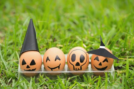 cup four: Four halloween egg in egg cup on green grass