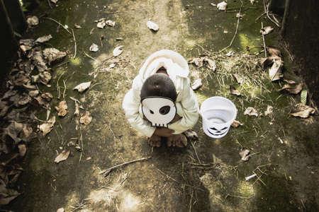 alone in the dark: Poor kids play Halloween with the mask handmade alone dark tone Stock Photo