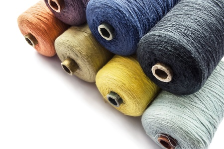 Bobbins of multicolor cotton thread on withe background photo