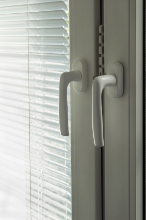 Part of closed white window with closed blinds and two handles closeup Stock Photo - 21584446