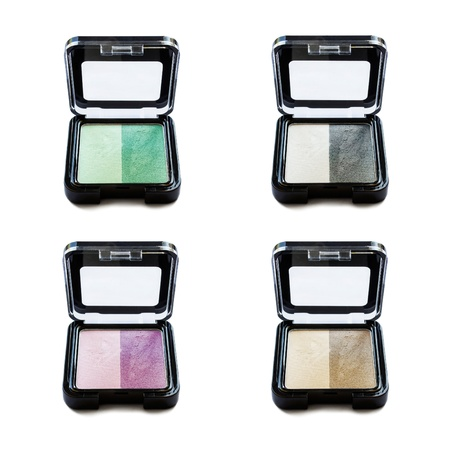 Set of four bicolor eyeshadows in little boxes isolated over white photo