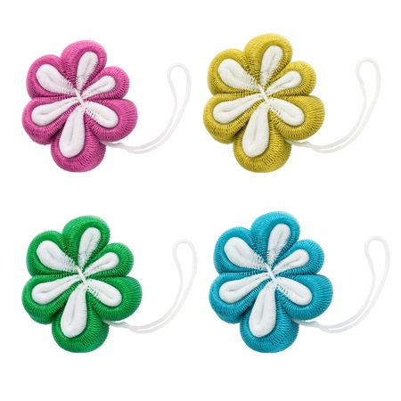 Set of four flower shaped bath sponges on white background photo