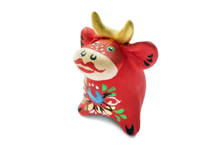 Ceramic painted statuette of red cow on white background photo