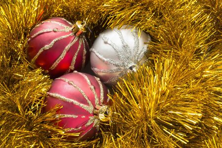 frippery: Red and silver christmas balls in garlands of golden tinsel