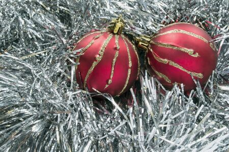 frippery: Pair of red christmas balls on silver tinsel as a background Stock Photo