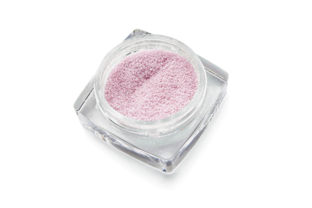 Glass transparent jar with pink eyeshadows on white background photo