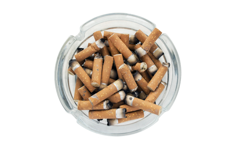 Glass ashtray full of cigarette butts on white background photo