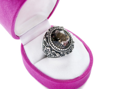 Part of opened pink jewel box with silver morion ring inside closeup photo