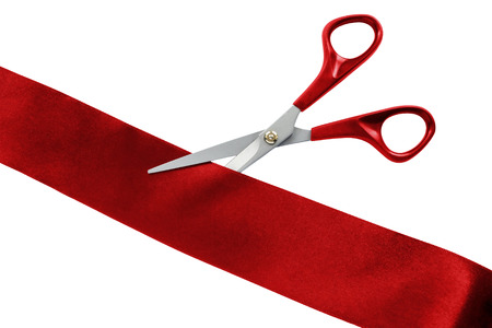 Scissors cut red silk ribbon on white background photo