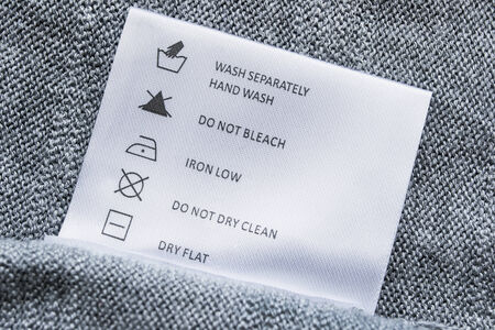 Label with washing instructions on gray knitted fabric photo