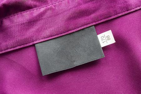 purple silk: Etiqueta negro en blanco en la tela de seda de color p�rpura Foto de archivo