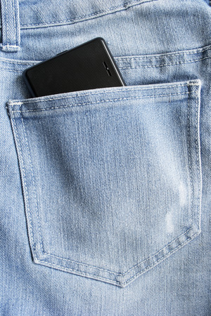 Black mobile phone in a jeans hip pocket photo