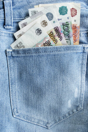 Some ruble banknotes of different value in a jeans hip pocket photo