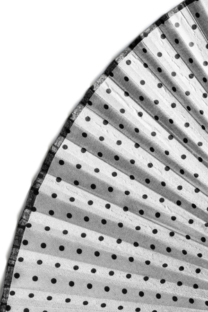 Part of opened textile white fan with black dots on white as a background photo