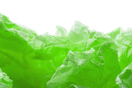 Green colorful crumpled paper over white as a background photo