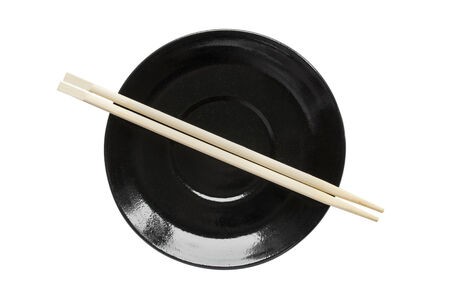Wooden chopsticks on black empty plate isolated over white photo