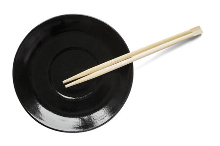 Black ceramic plate and wooden chopsticks on white background photo