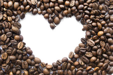 Brown coffee beans with white silhouette f a heart as a background photo