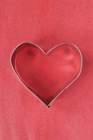 Metallic heart on red paper as a background photo