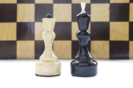 loss leader: Black king and white queen against chessboard as a background Stock Photo