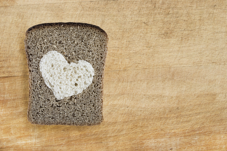Piece of rye bread with white heart on wooden board as a background photo