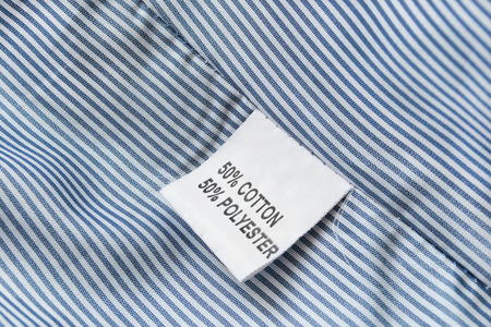 White fabric composition label on blue striped cloth as a background