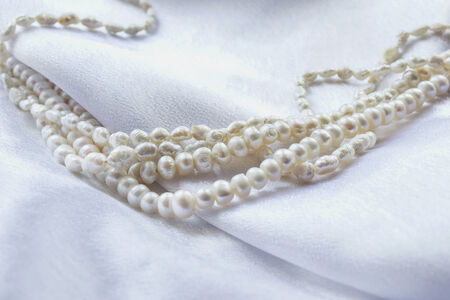 Strings of white pearl on white draped silk as a background photo
