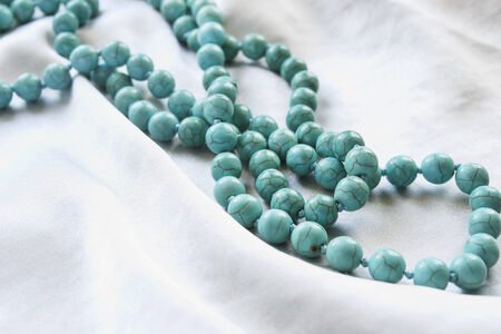 Strings of turquoise beads on white silk as a background photo