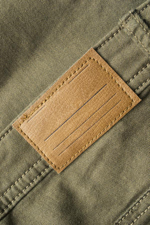 leather label: Blank leather label on khaki pants closeup as a background