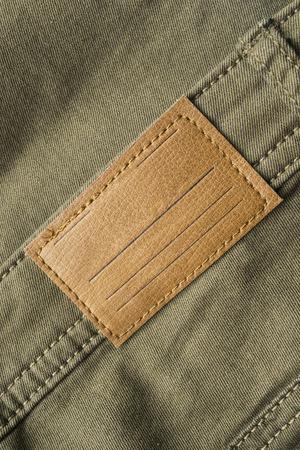khaki pants: Blank leather label on khaki pants closeup as a background